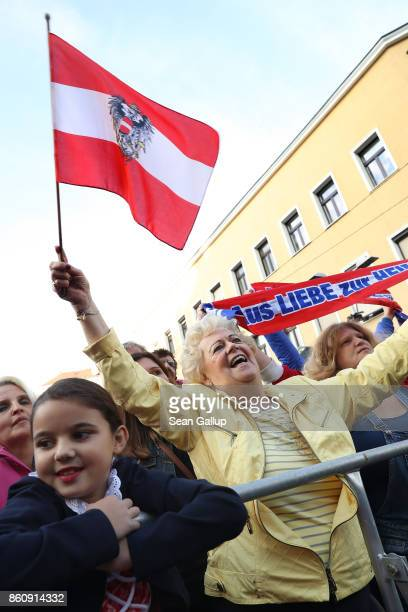Supporters of HeinzChristian Strache lead candidate of the rightwing Austria Freedom Party hold an Austrian flag and a banner that reads Out of love...