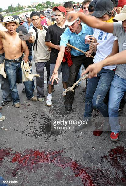 Supporters of Honduran President Manuel Zelaya show a bloodstain on the ground after a protestor was shot by Honduran soldiers outside Toncontin...