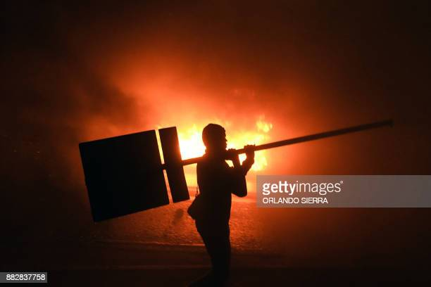 Supporters of Honduran presidential candidate for the Opposition Alliance against the Dictatorship party Salvador Nasralla, set a barricade alight...