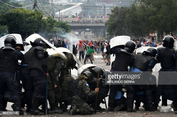 TOPSHOT Supporters of Honduran presidential candidate for the Opposition Alliance against the Dictatorship coalition Salvador Nasralla clash with...