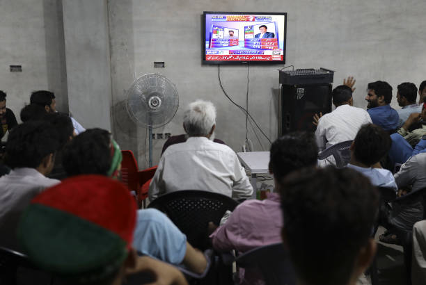 Supporters of Imran Khan head of the Pakistan TehreekeInsaf also known as Movement for Justice watch exit poll results on a television in Lahore...