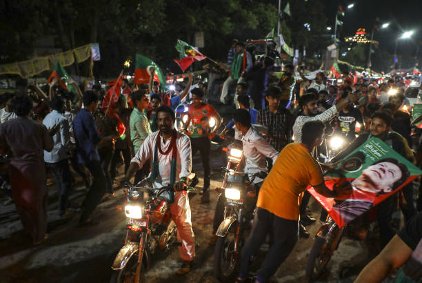 Supporters of Imran Khan head of the Pakistan TehreekeInsaf also known as Movement for Justice wave flags while celebrating on a street in Lahore...