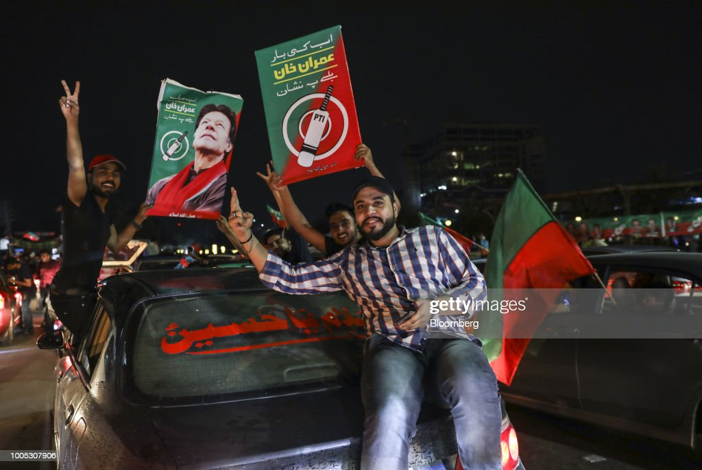 Supporters of Imran Khan head of the Pakistan TehreekeInsaf also known as Movement for Justice wave signs and flags while celebrating on a street in..