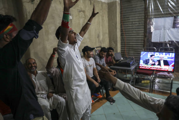 Supporters of Imran Khan head of the Pakistan TehreekeInsaf also known as Movement for Justice cheer while watching exit poll results on a television.