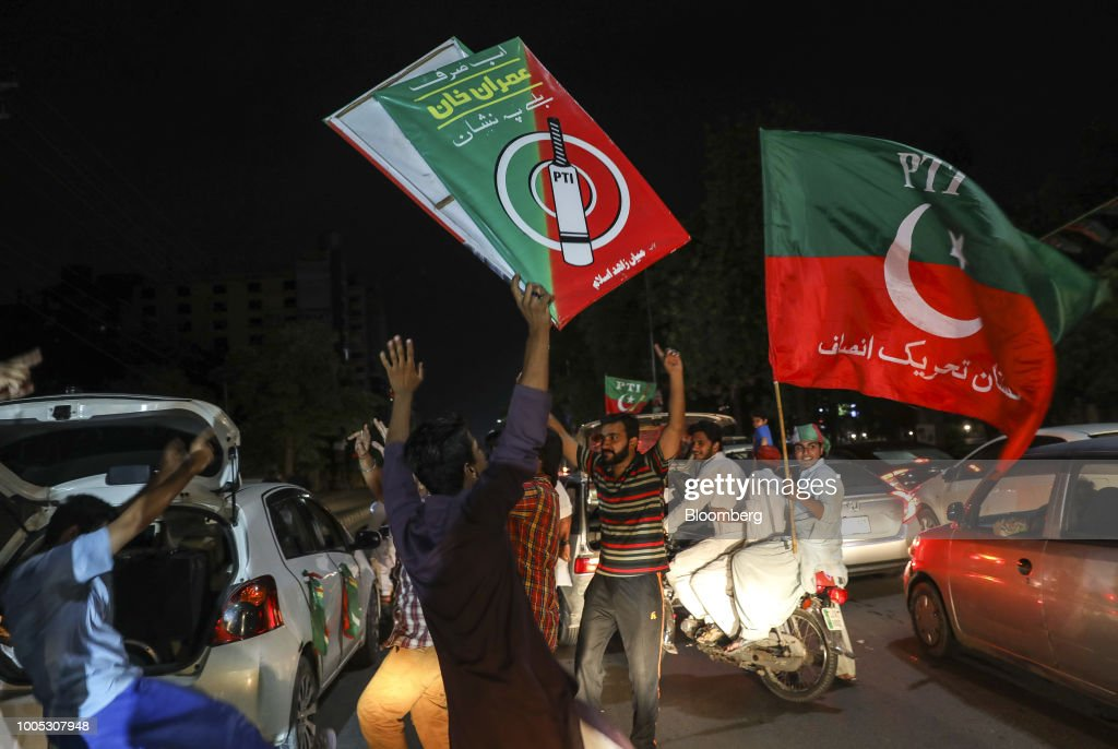 Supporters of Imran Khan head of the Pakistan TehreekeInsaf also known as Movement for Justice wave flags and signs while celebrating on a street in..