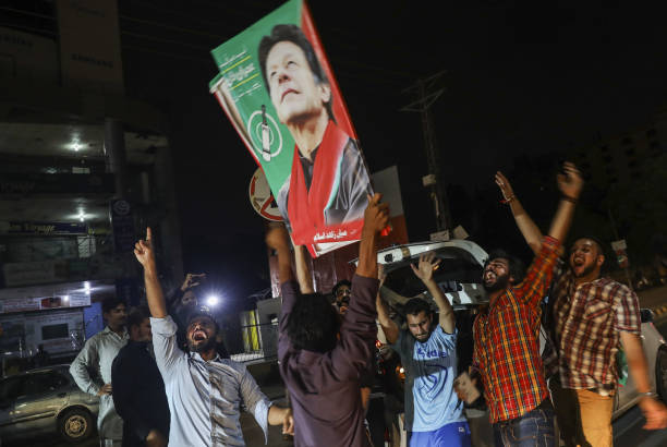 Supporters of Imran Khan head of the Pakistan TehreekeInsaf also known as Movement for Justice hold signs while celebrating on a street in Lahore...