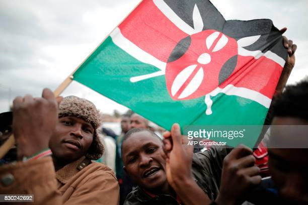 Supporters of incumbent Kenyan pesident Uhuru Kenyatta hold a Kenyan flag as they wait for the announcement of the presidential election's final...
