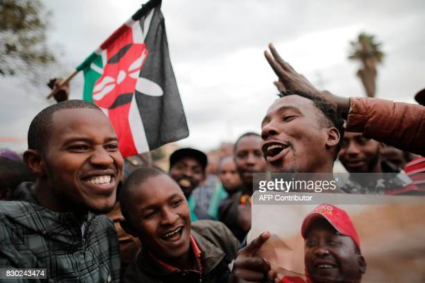 Supporters of incumbent Kenyan pesident Uhuru Kenyatta hold his portrait and a Kenyan flag as they wait for the announcement of the presidential...