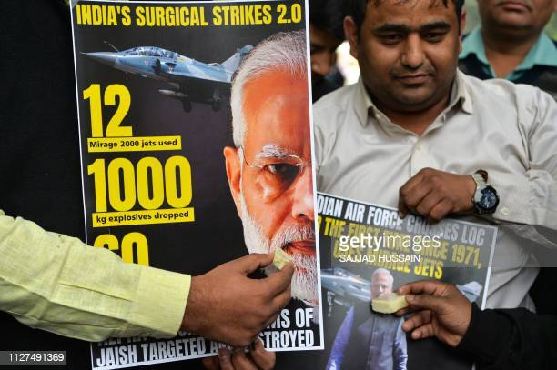 Supporters of Indian Prime Minister Narendra Modi offer sweets to a poster displaying his portrait in New Delhi on February 26 as they celebrate the...