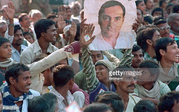 Supporters of Indian Prime Minister Rajiv Gandhi hold a poster of him at a rally in support of the victims of the Union Carbide leak in Bhopal which...
