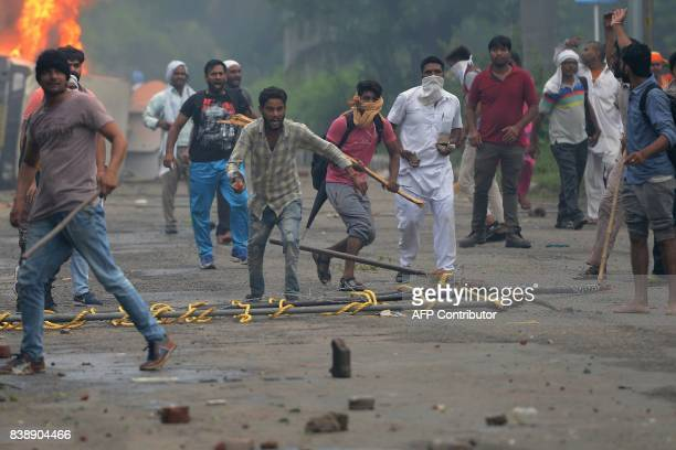 Supporters of Indian religious leader Gurmeet Ram Rahim Singh clash with security forces next to burning vehicles in Panchkula on August 25 2017 At...