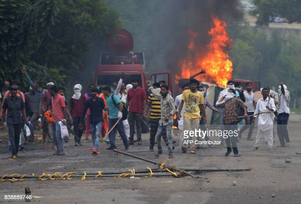 Supporters of Indian religious leader Gurmeet Ram Rahim Singh throw stones at security forces next to burning vehicles during clashes in Panchkula on...