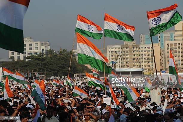 Supporters of Indian social activist Anna Hazare wave their national flags after after Hazare announced he would conclude his fast at the Mumbai...