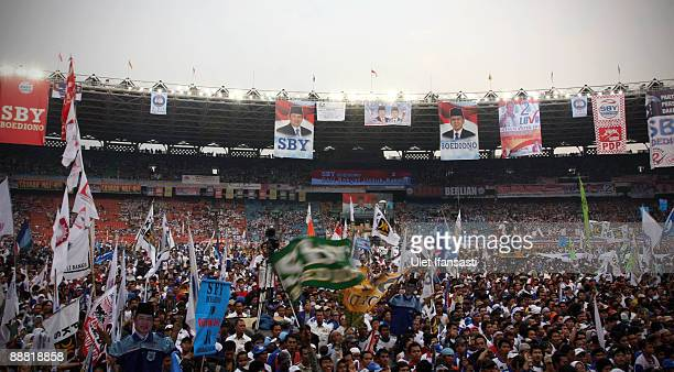 Supporters of Indonesian President and Democratic Party leader Susilo Bambang Yudhoyono cheer wave flags and signs during the final stages of the...