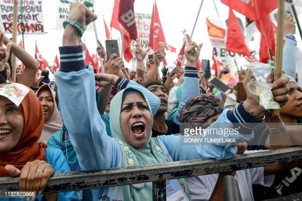 TOPSHOT Supporters of Indonesian presidential candidate Prabowo Subianto react during a campaign rally in Denpasar on Indonesia's resort island of...