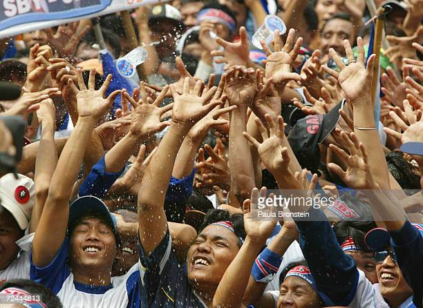 Supporters of Indonesian presidential candidate Susilo Bambang Yudhoyono raise their hands and reach for cups of water in the searing heat during his...