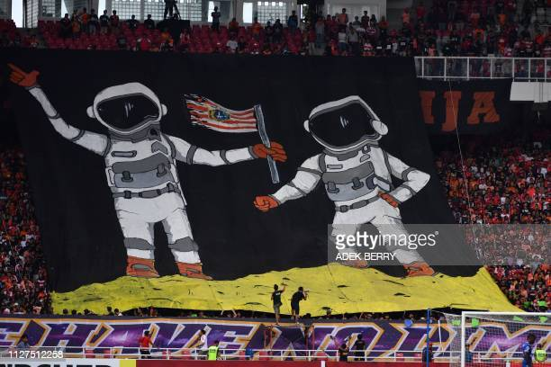 TOPSHOT Supporters of Indonesia's Persija Jakarta hold a big banner in support of their team against Vietnam's Becamex Binh Duong during their AFC...