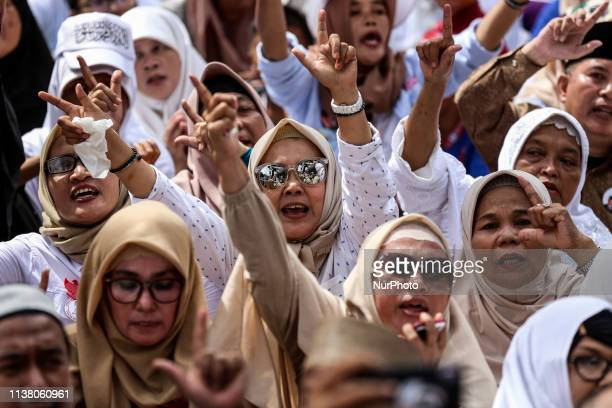 Supporters of Indonesia's presidential candidate Prabowo Subianto react as he delivers a speech declaring his victory after this week's presidential...