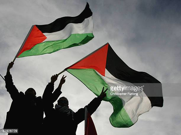Supporters of Interim Palestinian leader Mahmoud Abbas cheer and wave flags after Abbas placed his vote in the ballot box at the polling station in...