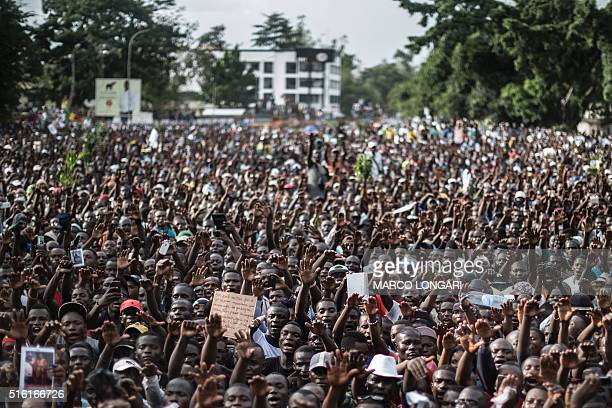 Supporters of Interim President of the Congolese Movement for Democracy and Integral Development Guy Brice Parfait Kole wave during a political rally...