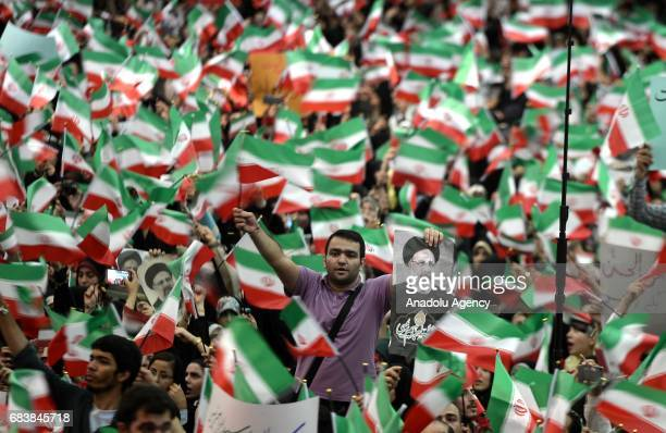 Supporters of Iranian cleric and presidential candidate Ebrahim Raisi wave flags during a rally prior to presidential elections in Tehran Iran on May...