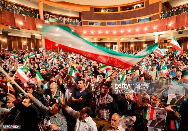 Supporters of Iranian conservative presidential candidate Mohammad Bagher Ghalibaf wave national flags during a campaign rally in the capital Tehran...
