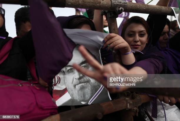 Supporters of Iranian President and candidate in the upcoming presidential elections Hassan Rouhani hold his portrait during a campaign rally at...