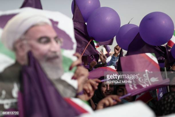 Supporters of Iranian President and candidate in the upcoming presidential elections Hassan Rouhani hold purple flags and balloons during a campaign...