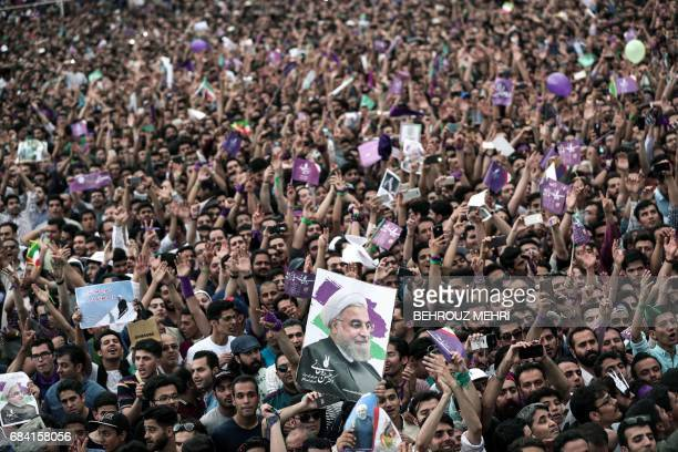 TOPSHOT Supporters of Iranian President and candidate in the upcoming presidential elections Hassan Rouhani raise his portrait as they attend a...