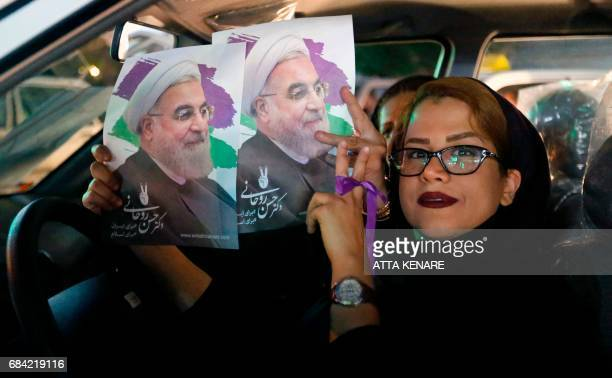 Supporters of Iranian President and election candidate Hassan Rouhani show his posters out of car windows ahead of the Iranian presidential election...