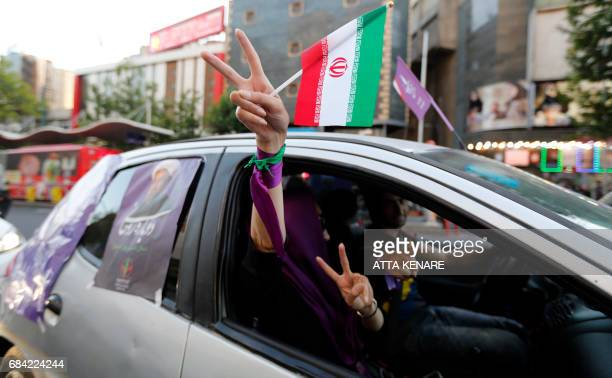 Supporters of Iranian President and election candidate Hassan Rouhani raise the victory gesture as they show his posters out of car windows ahead of...