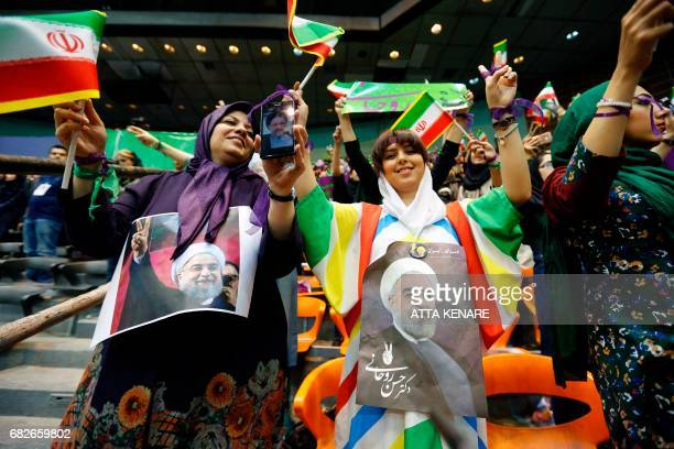 Supporters of Iranian President and presidential candidate Hassan Rouhani hold up his portrait during a campaign rally in the capital Tehran on May...