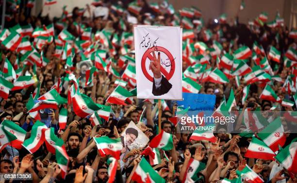 Supporters of Iranian presidential candidate Ebrahim Raisi wave national flags as they raise a sign reading in Persian 'we do not repeat mistakes'...