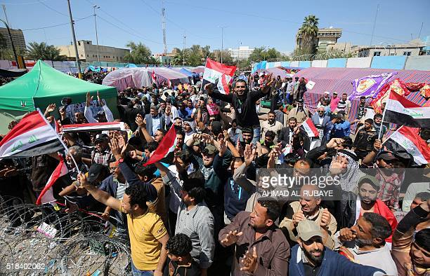 Supporters of Iraqi Shiite cleric Moqtada alSadr wave their national flag as they protest outside the heavily fortified Green Zone in Baghdad on...