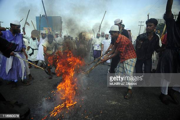 Supporters of Islamic political parties protest as they set a fire alight on street on the outskirts of Dhaka on July 10 2011 Police fired rubber...