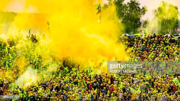 Supporters of Italian Yamaha rider Valentino Rossi light flares during the Moto GP race at the Grand Prix of Germany at the Sachsenring Circuit on...