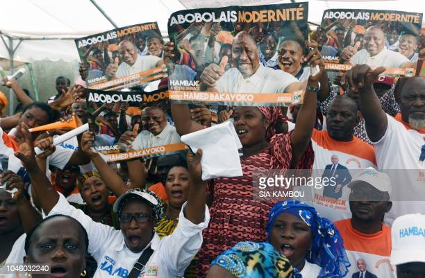 Supporters of Ivorian Defence Minister and local elections candidate for Abidjan's Abobo district Hamed Bakayoko also known as Hambak hold up his...