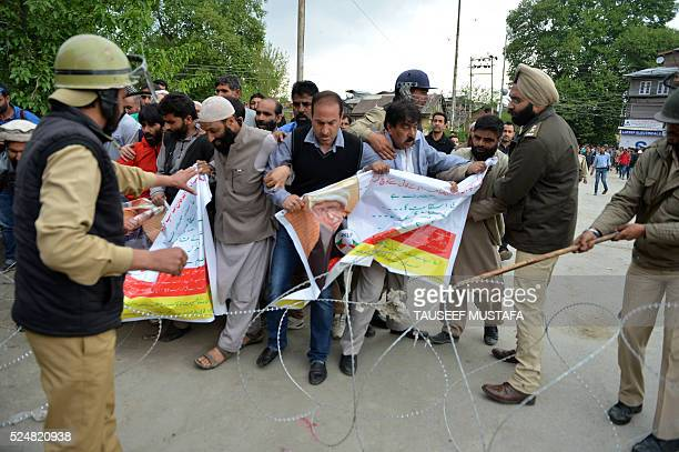 Supporters of Jammu and Kashmir Libration Front scuffle with Indian police as they try to cross a barbed fence wire during a march towards Lal Chowk...