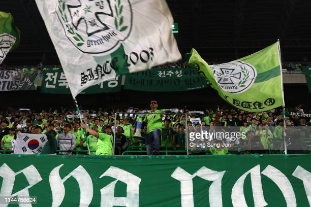 Supporters of Jeonbuk Hyundai Motors cheer during the AFC Champions League Group G match between Jeonbuk Hyundai Motors and Urawa Red Diamonds at...