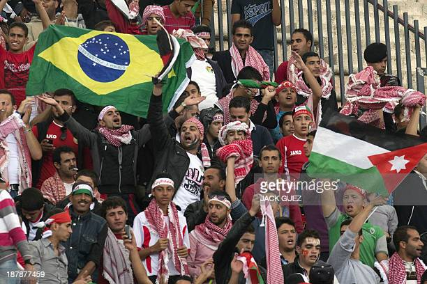 Supporters of Jordan cheer their team before the FIFA 2014 World Cup qualifier football match Uruguay against Jordan at the International Stadium on...