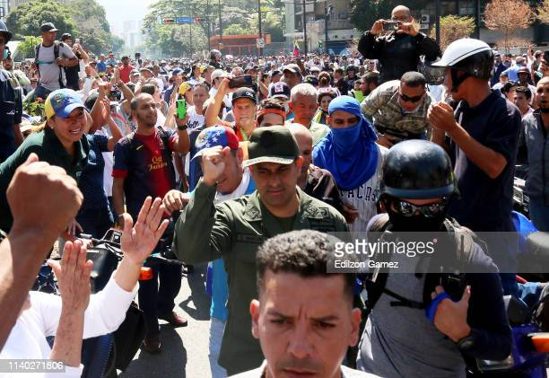 Supporters of Juan Guaido march near the air force base La Carlota on April 30 2019 in Caracas Venezuela Through a live broadcast via social media...