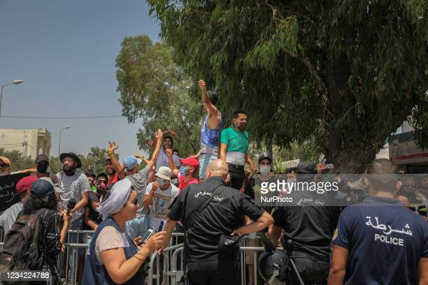 Supporters of Kais Saied chant slogans as they lift fist in front of the riot police, during a demonstration held in front of the building of the...
