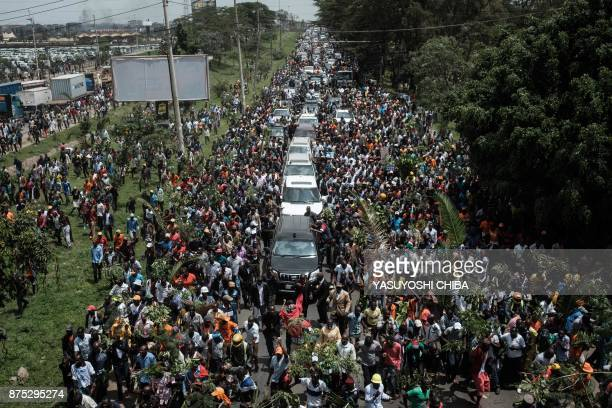 TOPSHOT Supporters of Kenyan's opposition party National Super Alliance leader Raila Odinga march with his convoy upon his arrival from the Jomo...