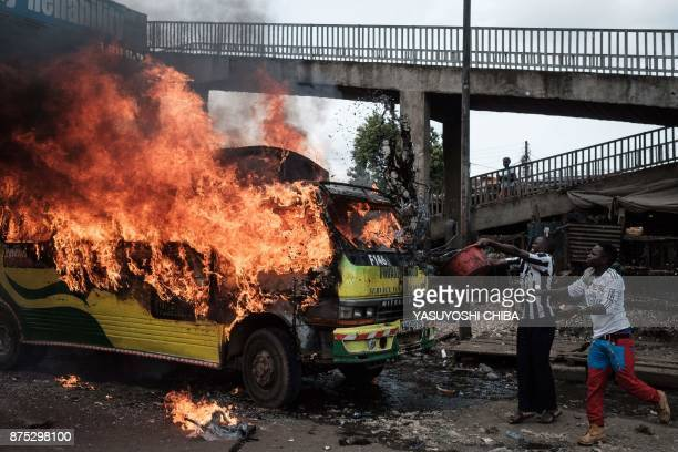 TOPSHOT Supporters of Kenyan's opposition party National Super Alliance throw water onto a burning bus during a demonstration on November 17 2017 in...