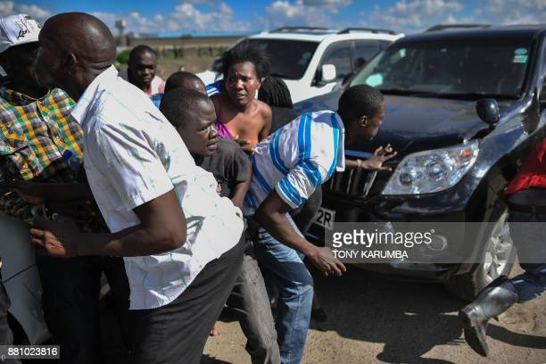 Supporters of Kenya's opposition leader take cover between vehicles of the leader's entourage as they attempt to flee from teargas fired by antiriot...