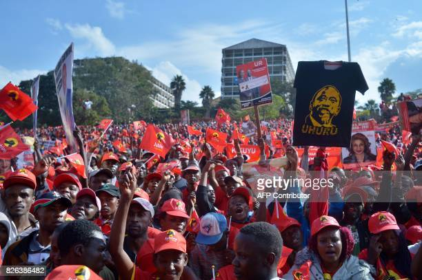 Supporters of Kenya's ruling President and candidate to his own succession Uhuru Kenyatta wave flags during a campaign rally for his Jubilee Party of...