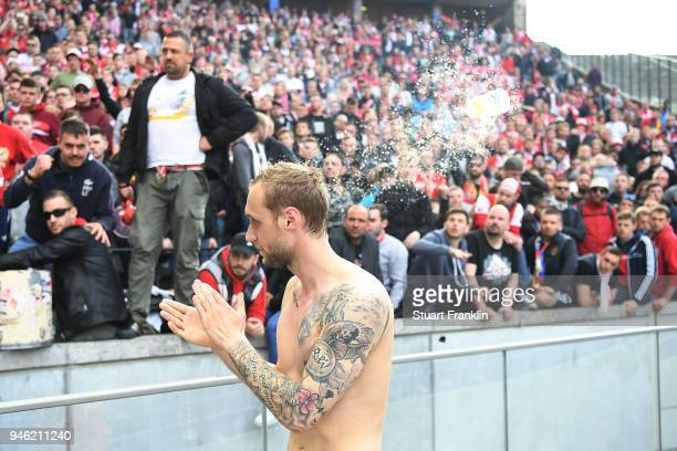 Supporters of Koelen show their feelings about their team while a bear cup is thrown at Marcel Risse of Koeln after the Bundesliga match between...