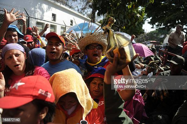 Supporters of late Venezuelan President Hugo Chavez cheer as members of the National Guard distribute goods in Caracas on March 8 2013 Venezuela gave...