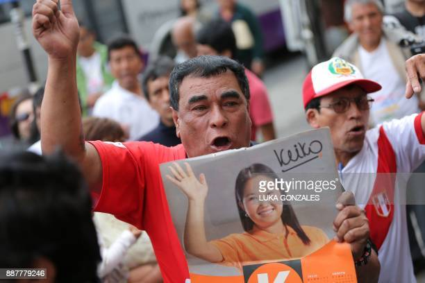 Supporters of leader of Fuerza Popular party Keiko Fujimori protest outside one of their party locals in Lima while police officers and prosecutor's...