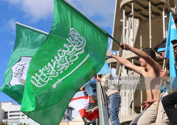 Supporters of Lebanese prime minister Saad Hariri wave the Saudi flag alongside the Future Movement flag as they gather at his home in Beirut on...